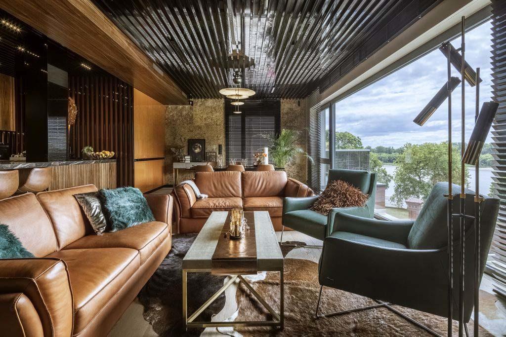 Wygodna, duża sofa ze skóry w odcieniu delikatnego pomarańczu idealnie komponuje się   z ciemną zielenią foteli oraz z jasnobrązową podłogą.