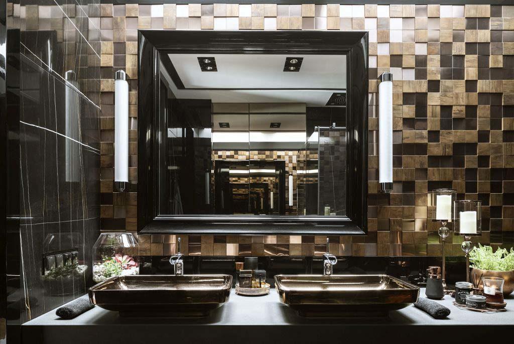 Lustro w czarnej ramie, dwie umywalki nablatowe z piękną armaturą łazienkową tworzą harmonijną całość z elementami złota i miedzi.